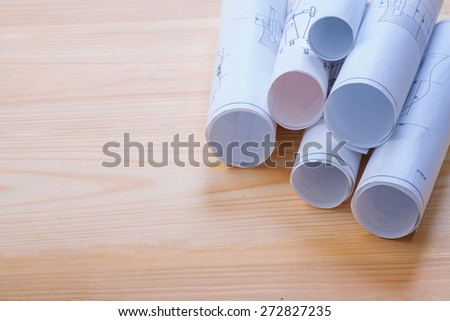 big stack of rolls blueprints on wooden board with organized copyspace  - stock photo