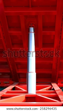 big stainless steel Hydraulic cylinder ton below the red caisson tipper truck - stock photo