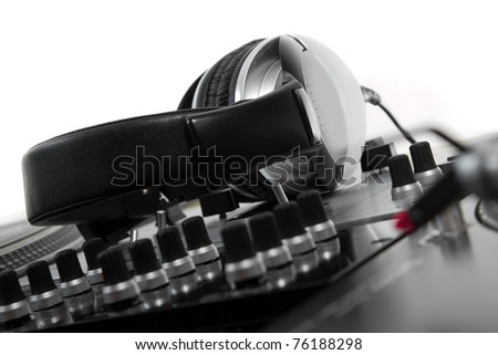 Big stereo headset for a professional disc jockey laying on mixing controller - stock photo