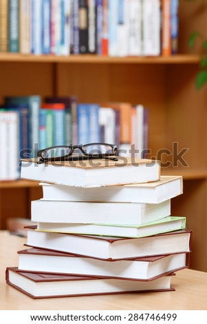 Big stock of books standing on the table in a library with glasses on the top, bookshelves on a background, selective focus, close up - stock photo