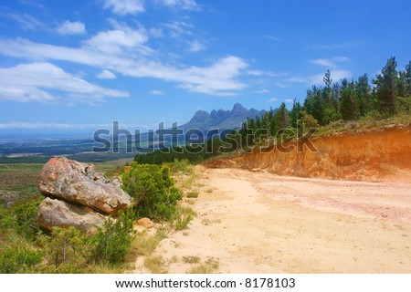 Big stone next to road in amazing mountains. Shot in Hottentots Holland Mountains, Vergelegen area, near Somerset West, Western Cape, South Africa. - stock photo