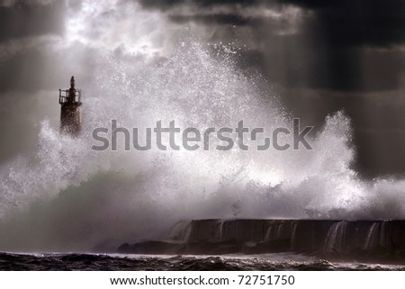 Big storm wave against lighthouse of Vila do Conde, north of Portugal (enhanced sky)