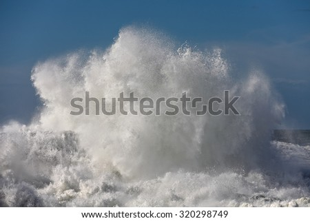 Big stormy sea wave crashing against a pier from the north of Portugal - stock photo