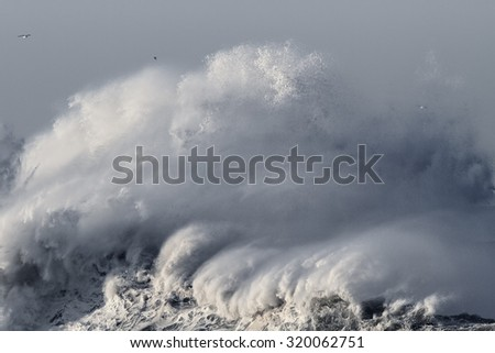 Big stormy sea wave crashing against northern portuguese coast. Converted black and white and toned blue. - stock photo