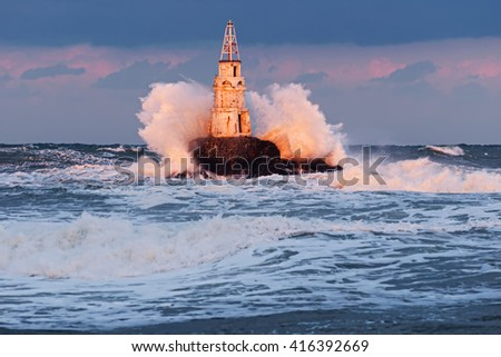 Big stormy wave against lighthouse in the Achtopol Bay, Bulgaria - stock photo