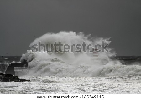 Big stormy wave against pier and beacon of the harbor of the entry of Douro river (Porto, Portugal)