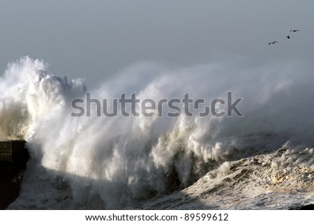 Big stormy wave against pier and lighthouse in the north of Portugal near mouth of river Douro in Porto