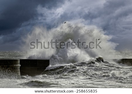 Big stormy waves against pier from the north of Portugal. Enhanced sky.  - stock photo