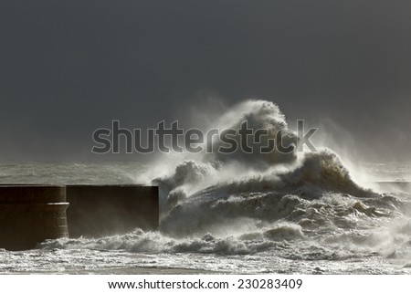 Big stormy waves against pier with interesting light. Porto, Portugal.  Low edition photo.
