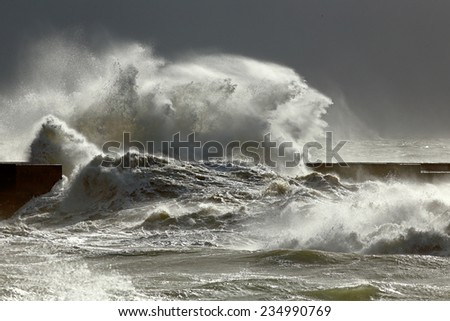 Big stormy waves against pier with interesting light. Porto, Portugal.  Low edition photo. - stock photo