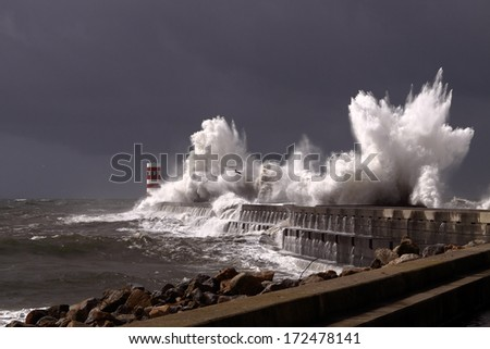 Big stormy waves over a pier and lighthouse, Porto, Portugal - stock photo