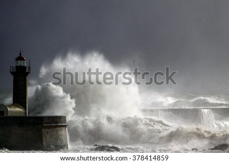 Big stormy waves over old lighthouse and pier of Douro river mouth with interesting light from a sunbeam filtered by sea spray against a sky before rain. Soft backlight. - stock photo