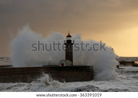 Big stormy waves over pier and lighthouse at winter sunset. Entry of Douro river mouth harbor, north of Portugal. - stock photo