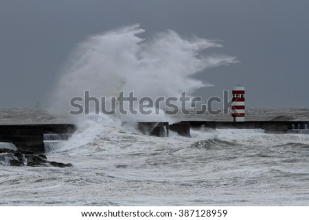 Big stormy white wave over lighthouse and pier against a rainy sky, north of Portugal - stock photo