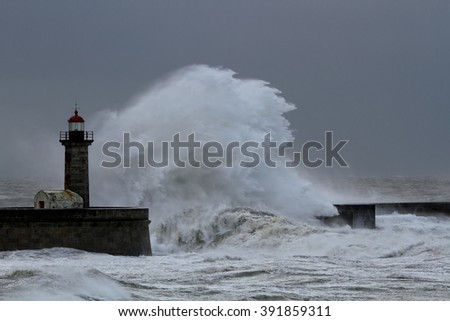 Big stormy white wave over old lighthouse and granite pier against a rainy sky, north of Portugal - stock photo
