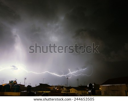 big strike in the sky with storm above a city