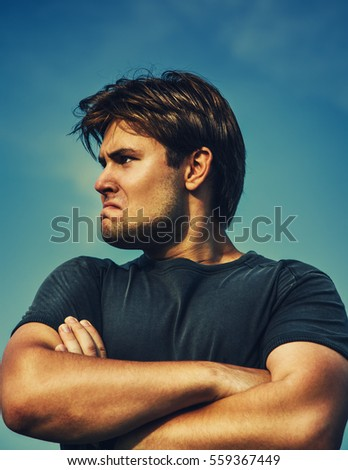Big strong and very angry man portrait looking aside. On blue sky background.