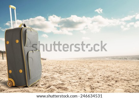 big suitcase of gray color and sand  - stock photo