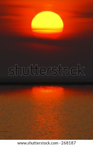 Big sun in water reflection - stock photo