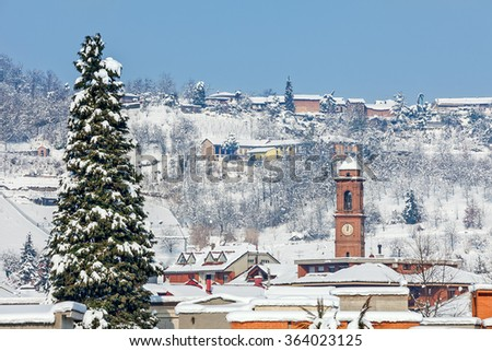Big tall tree and small italian town covered with snow on background in Piedmont, Northern Italy. - stock photo