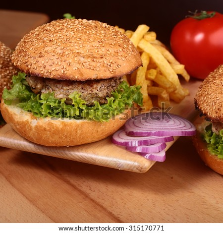 Big tasty appetizing fresh burger of green lettuce red tomato cheese and bacon slice meat cutlet and white bread bun with sesame seeds chips and violet onion closeup, square picture