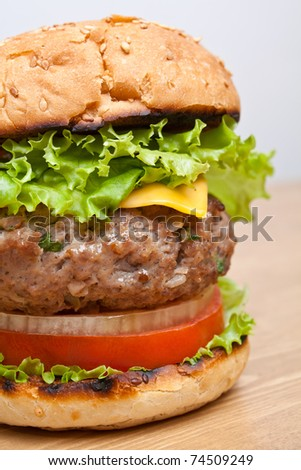 big tasty cheeseburger close-up on wooden table - stock photo