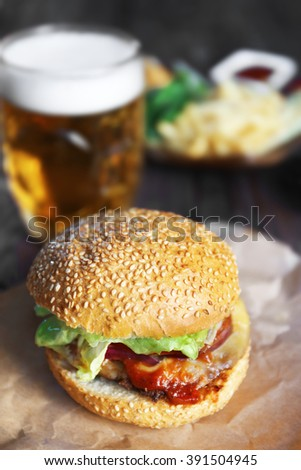 Big tasty hamburger on a paper with light beer in glass mug, close up - stock photo