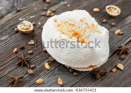 Big tasty meringue on rustic wooden background. Different spices around dessert - anise stars, coffee beans, walnuts and peanuts.