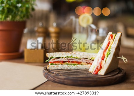big, tasty sandwich with ham, tomato, lettuce, cheese on the wooden plate in the restaurant - stock photo