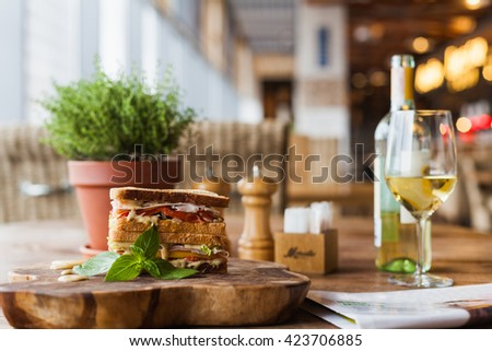 big tasty sandwich with sauce on the wooden plate in the restaurant