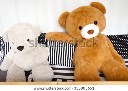 Big Teddy Bear Plush Dolls sitting together on the sofa with black and white stripe pillows, relax and cozy concept - stock photo