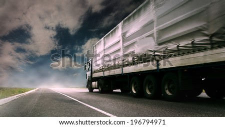 Big tented truck on the lonely highway - stock photo