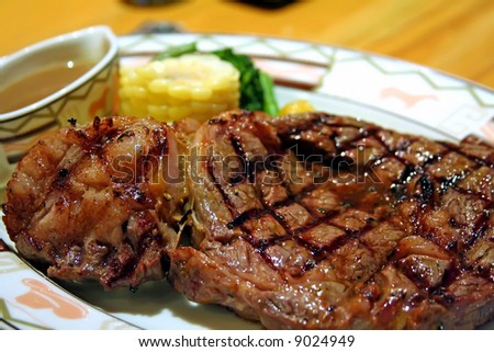 Big thick steak with garnishing corn and gravy - stock photo
