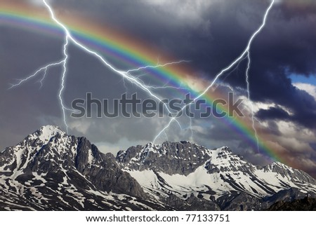 Big thundershower with ray and rainbow in the mountains - stock photo