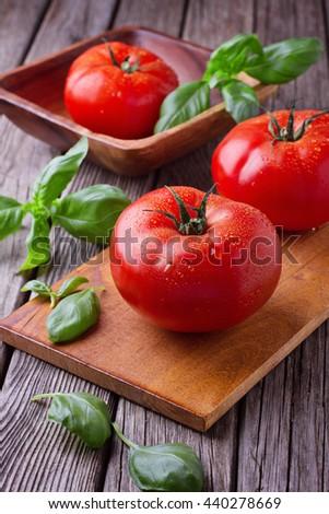 Big tomatoes with basil - stock photo