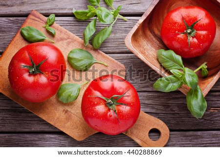 Big tomatoes with basil top view - stock photo