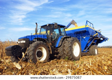 Big tractor working in a harvested maize field