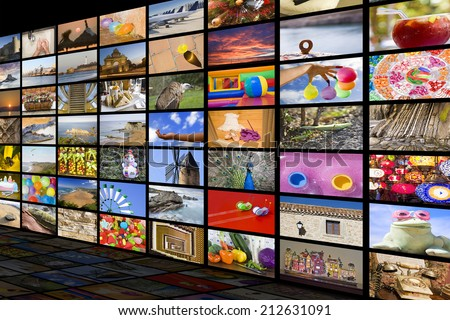 Big TV videowall with different channels in a black room with reflection - stock photo
