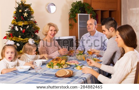Big united family at festive table near Christmas tree - stock photo