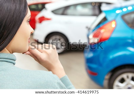 Big variety. Cropped closeup of a woman choosing a new car at the car salon looking thoughtfully making a decision  - stock photo