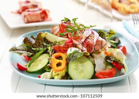 Big vegetable salad with Prosciutto cheese rolls - stock photo