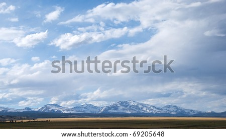 Big view of snowy mountains and vast open space under dramatic clouds near Kenosha Pass, Colorado - stock photo