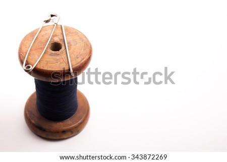 Big vintage spool of thread with needle isolated on white. Symbol of handmade, clothes and needlework.
