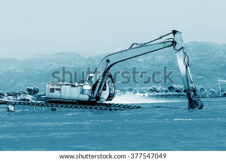 Big water excavator dredging sediment mud from river. Technical blue colored. - stock photo