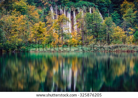 Big waterfall shot through autumnt forest over emerald lake with reflection. - stock photo