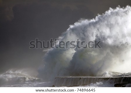 Big wave against a pier in the north of Portugal in a stormy overcast evening - mouth of river Ave in Vila do Conde - stock photo