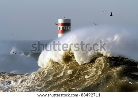 Big wave against beacon and pier in the north of Portugal in a stormy morning - mouth of river Douro, Porto - stock photo