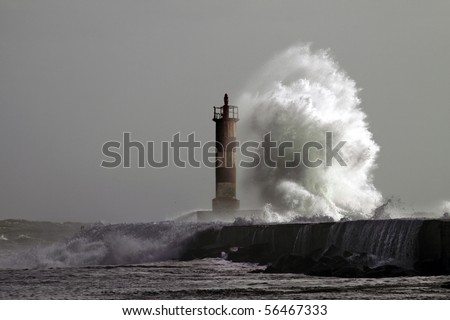 Big wave against lighthouse in the north of Portugal - stock photo