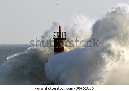 Big wave against lighthouse in the north of Portugal in a stormy overcast evening - mouth of river Ave in Vila do Conde - stock photo