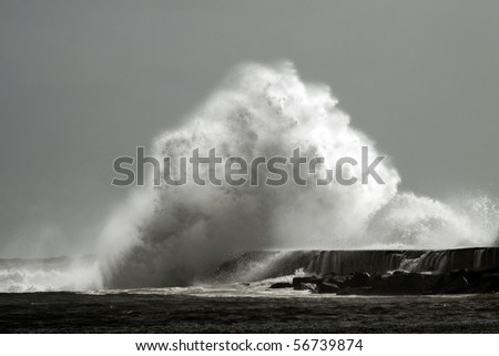 Big wave against little harbor in a stormy day in portuguese coast - stock photo